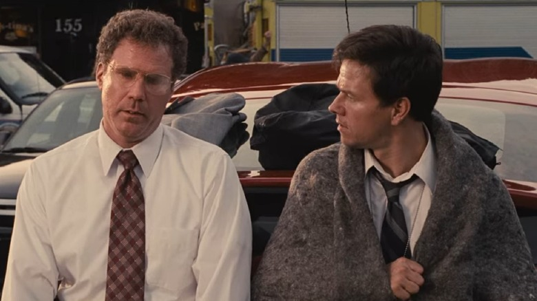 Will Ferrell and Mark Wahlberg sitting on car