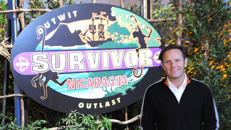 Mark Burnett next to Survivor logo