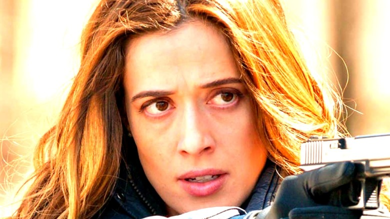 Marina Squerciati aiming her weapon