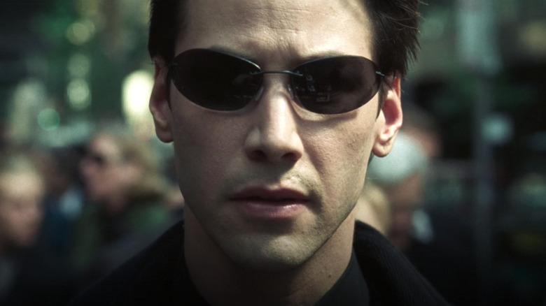 Keanu Reeves as Neo wearing sunglasses in The Matrix