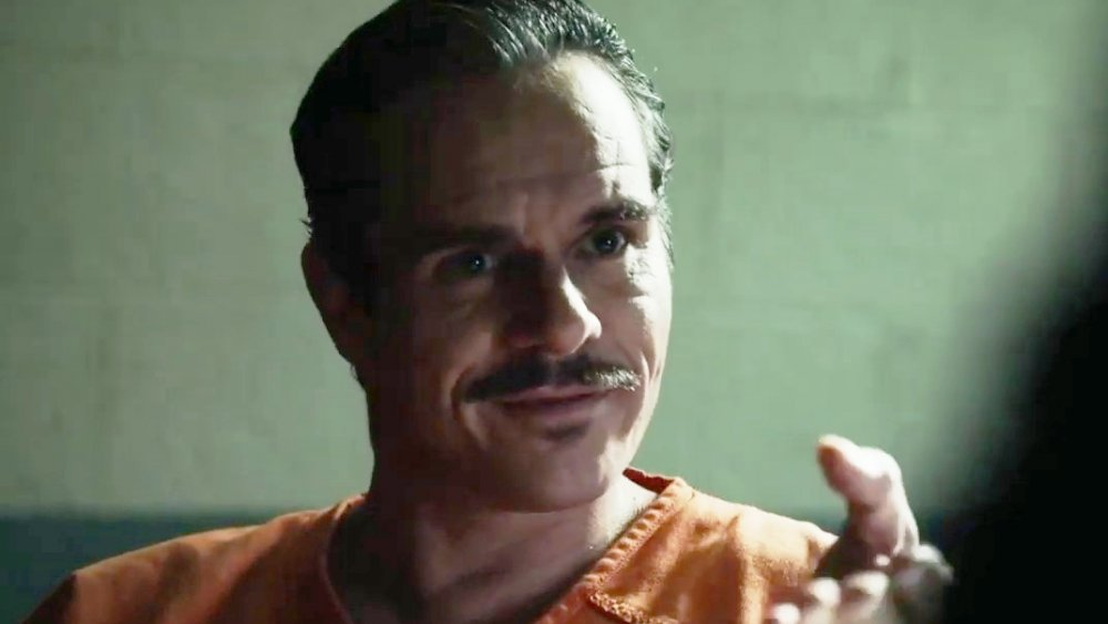 Tony Dalton as Lalo wears an orange prison uniform as he smiles and gestures towards someone off screen on Better Call Saul