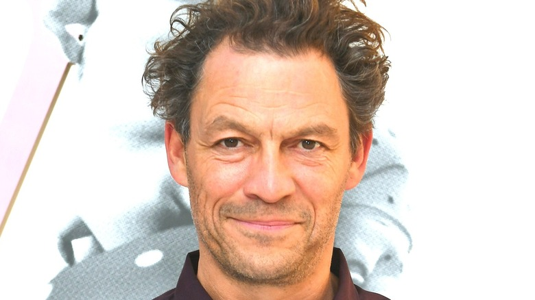 Dominic West smiling with white background