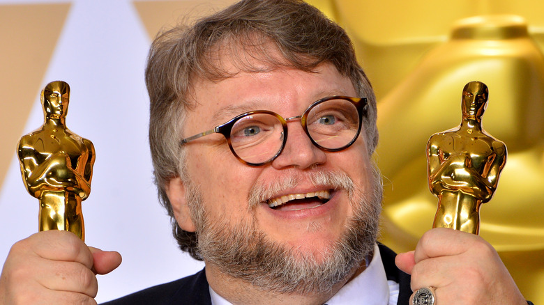 Guillermo del Toro holding two Oscars and smiling
