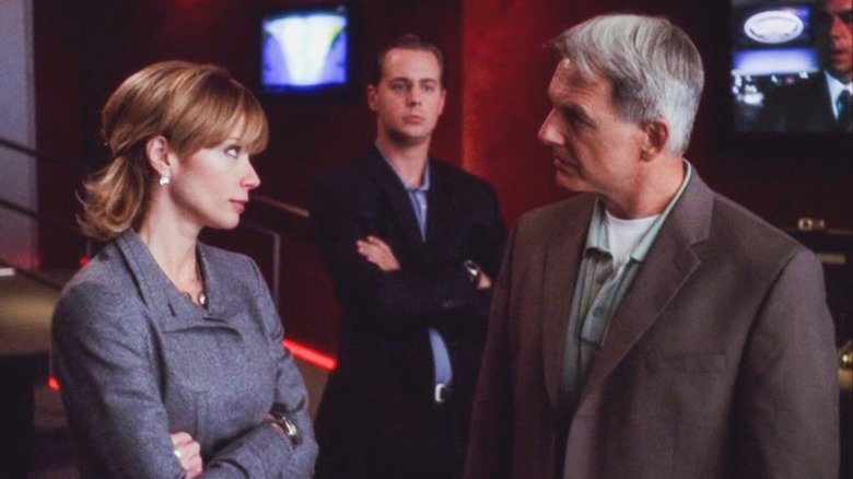 Lauren Holly as Jenny Shepard folds her arms and stares down Mark Harmon as Agent Gibbs while Sean Murray as Tim McGee watches in the background in NCIS