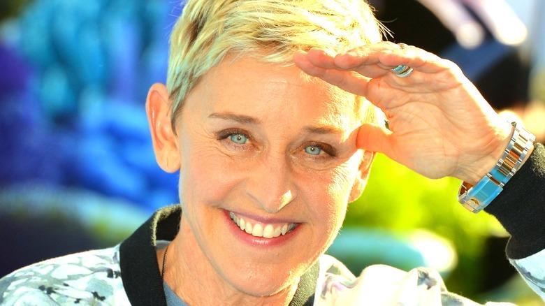 Ellen DeGeneres smiling and blocking sun with hand
