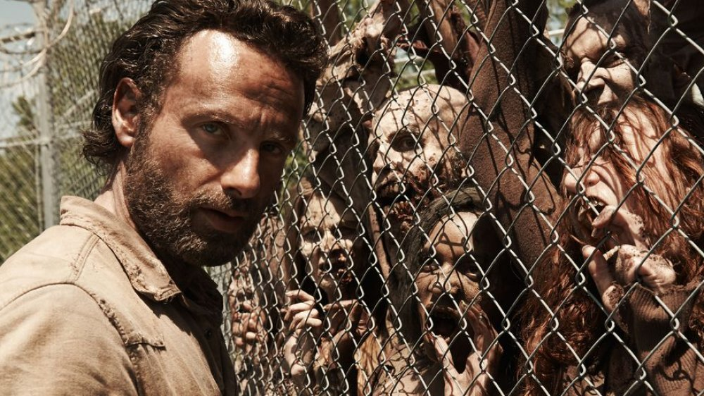 Andrew Lincoln as Rick Grimes on The Walking Dead beside walkers, not zombies