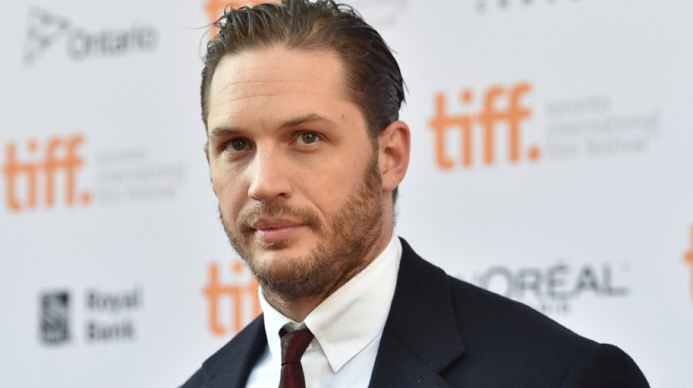 Tom Hardy appears on a carpet at the Toronto International Film Festival
