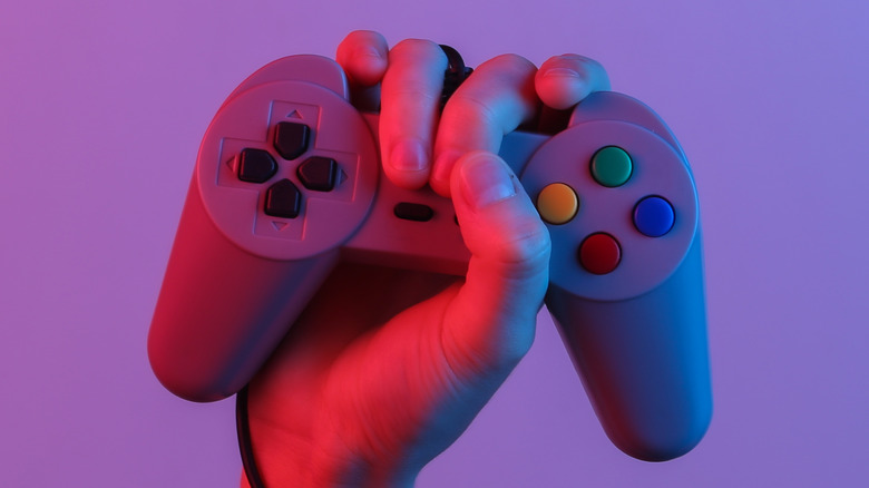 Hand holding PS1 controller
