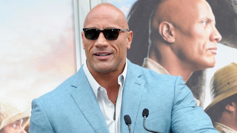 The Rock in sunglasses at podium