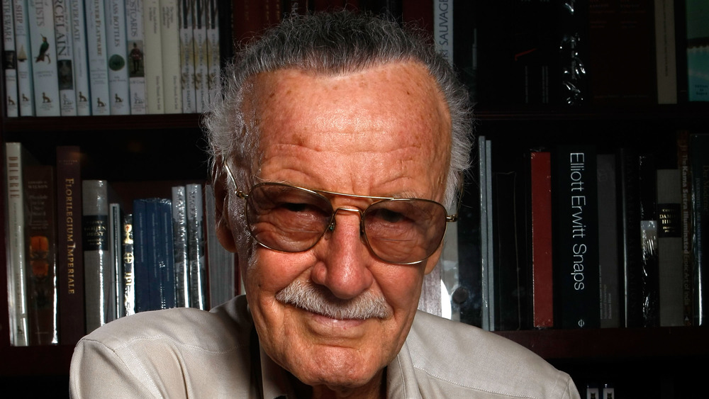 Stan Lee in front of a bookshelf