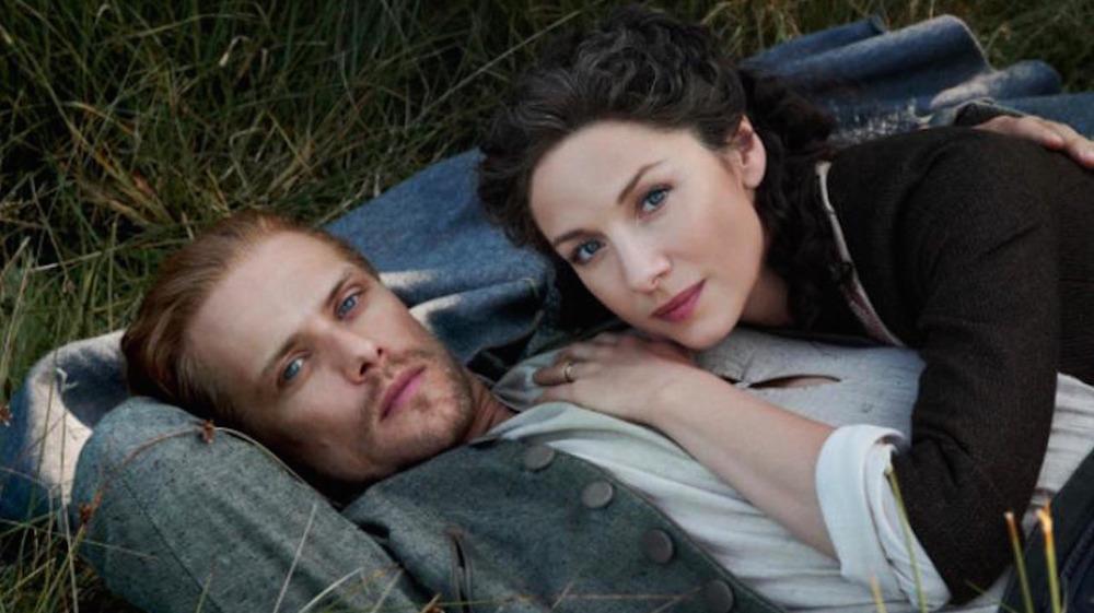 Caitríona Balfe and Sam Heughan lying on the grass