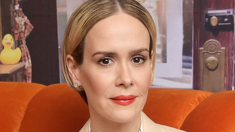 ECU of Sarah Paulson with orange lipstick on orange couch