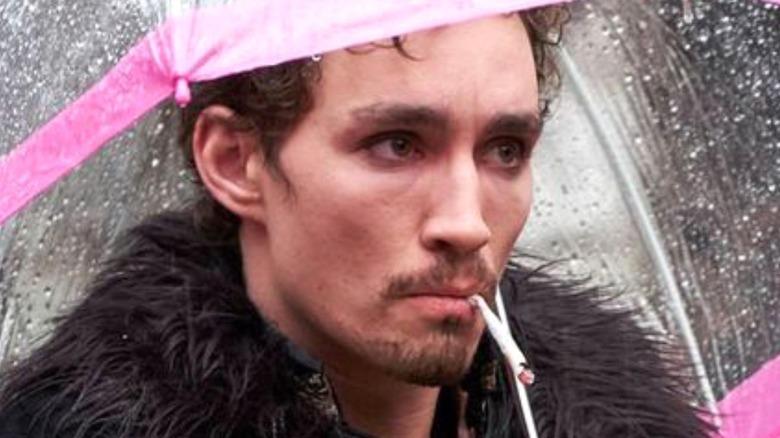 Klaus smoking under umbrella