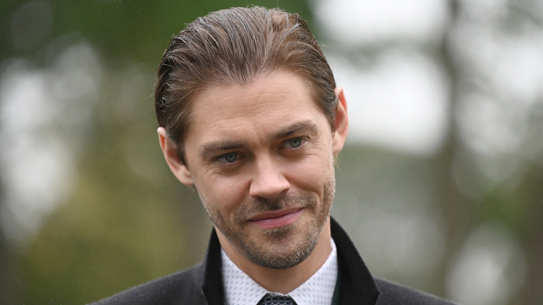 Tom Payne with slicked-back hair