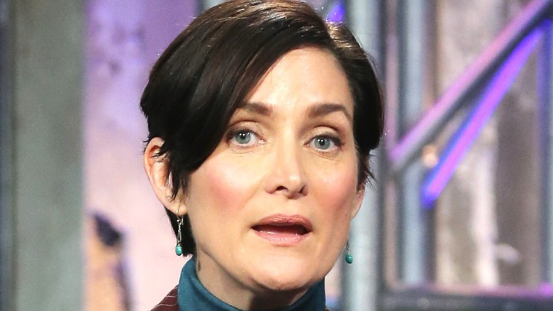 Carrie-Anne Moss with short hair and earrings