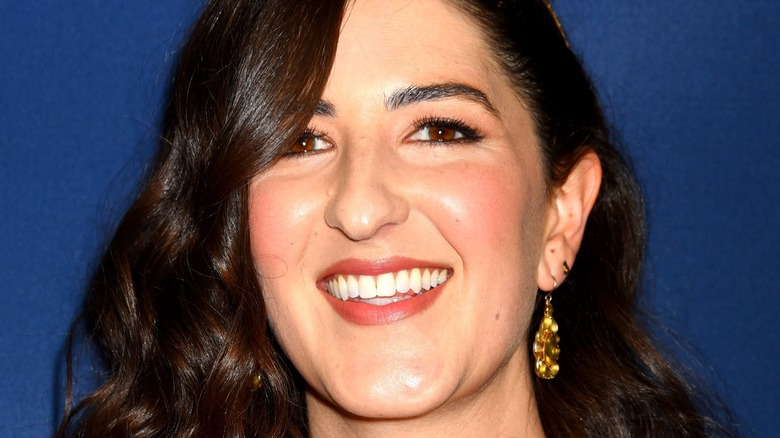 D'Arcy Carden smiling blue background