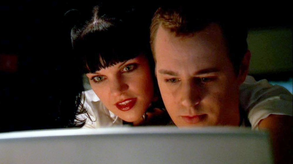 Pauley Perrette as Abby Sciuto leans over Sean Murray as Tim McGee while he uses a computer in NCIS