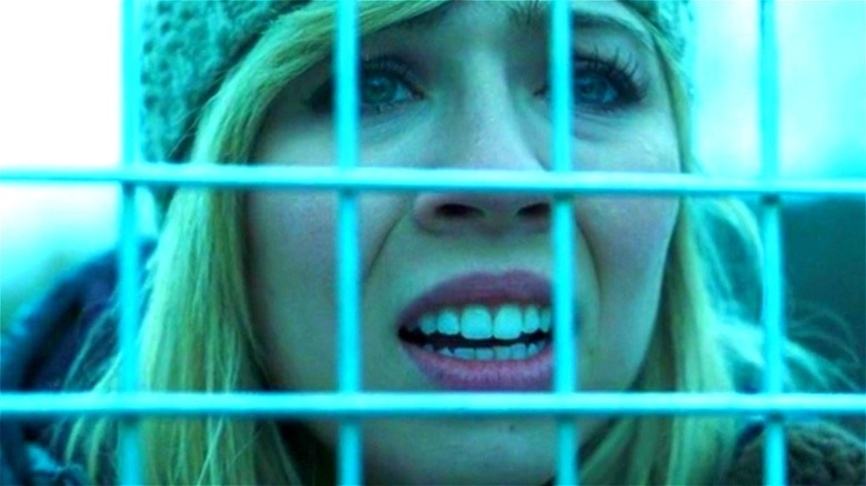 Wiley looking through a chain-link fence with a concerned look on her face