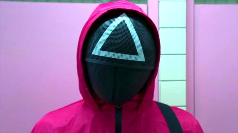Squid Game guard wearing triangle mask