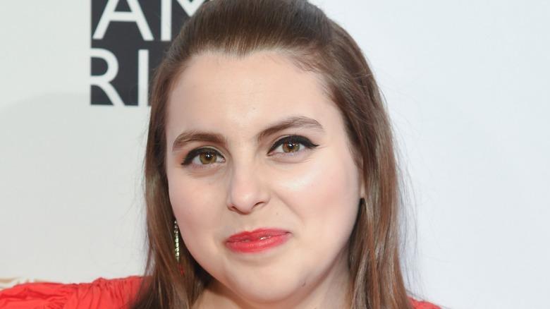 Beanie Feldstein smiling on red carpet