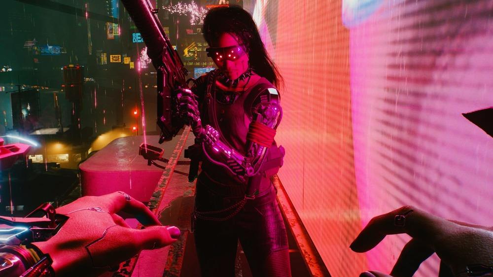Female character brandishes gun in Cyberpunk 2077