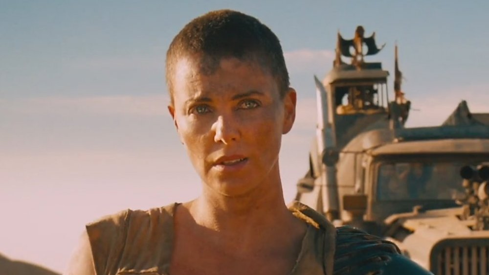 Charlize Theron as Furiosa, standing in front of truck in Mad Max: Fury Road