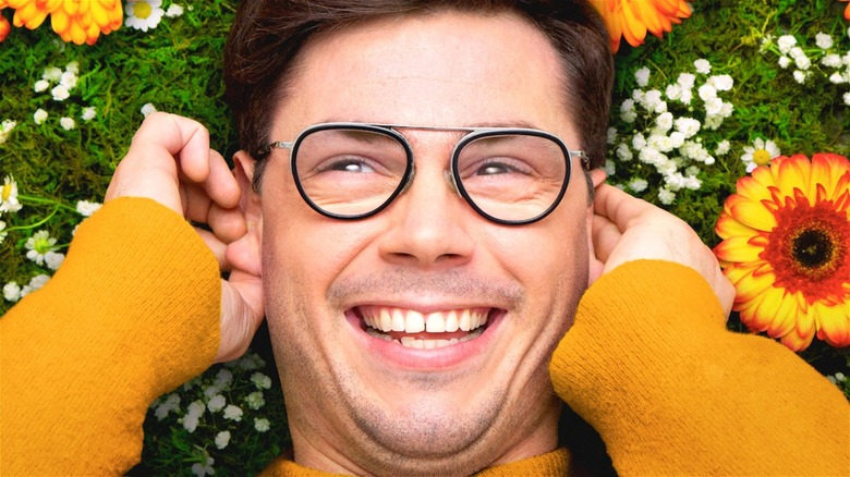 Ryan smiling in flowers