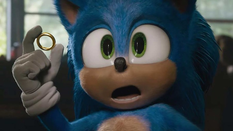Sonic holds a ring in his hand and looks at the camera in surprise