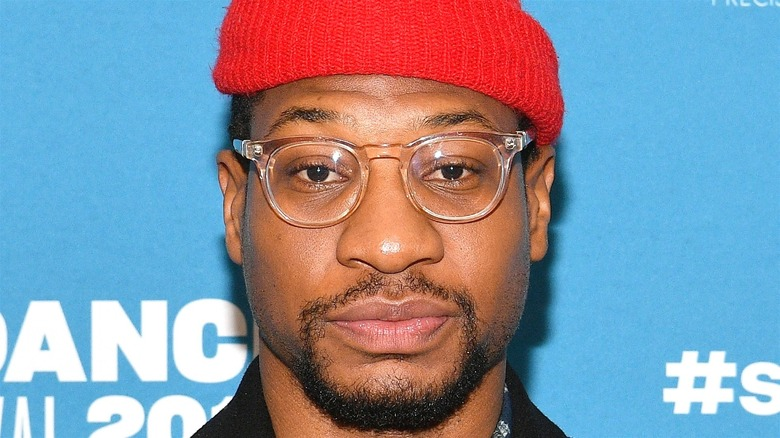 Jonathan Majors in a red cap