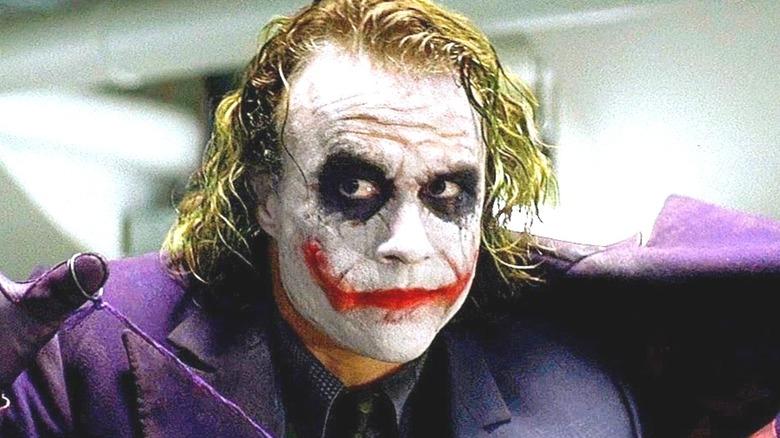 Joker holding his coat open