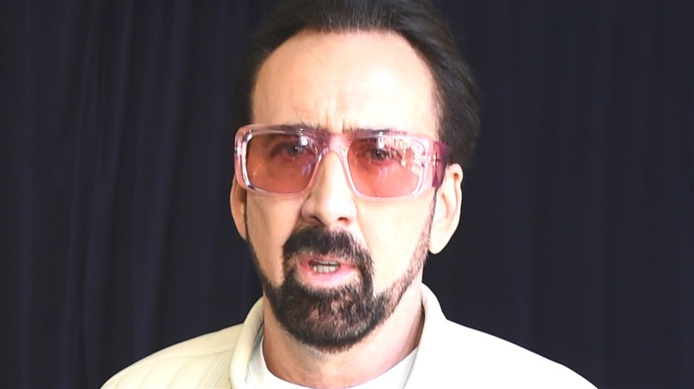 Nicolas Cage with red glasses and beard
