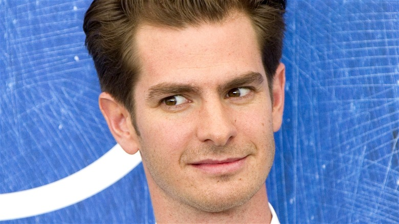 Andrew Garfield looking sideways with blue background