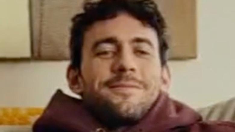 Man smiling while watching TV