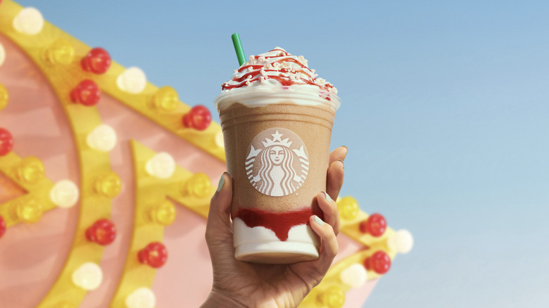 A hand holding the Starbucks Funnel Cake Frappuccino