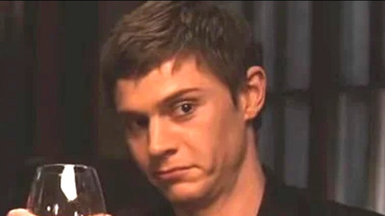 Evan Peters holding a drink
