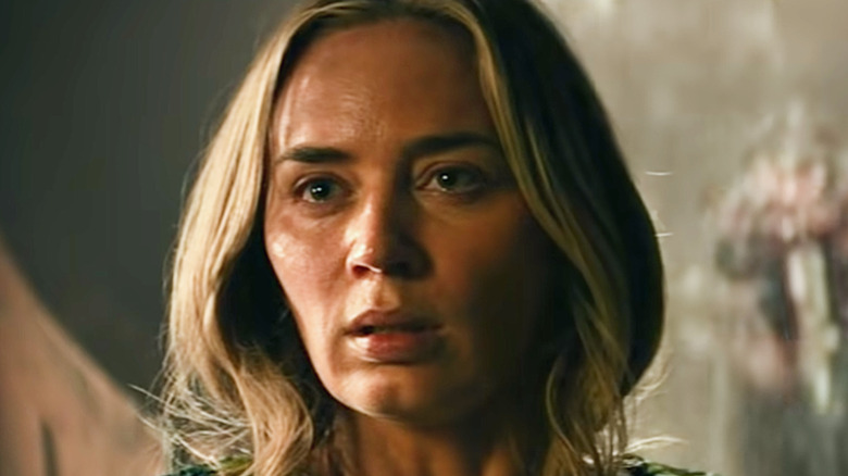 Emily Blunt scared with monster behind her