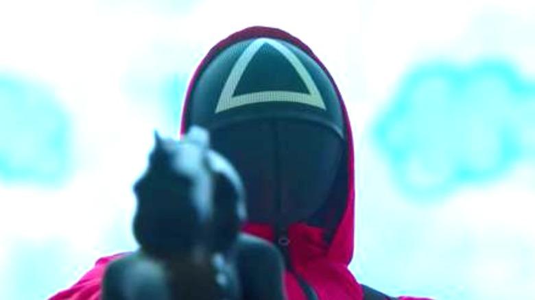 Triangle guard pointing a gun