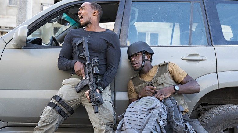 Anthony Mackie and Damson Idris take shelter behind a vehicle