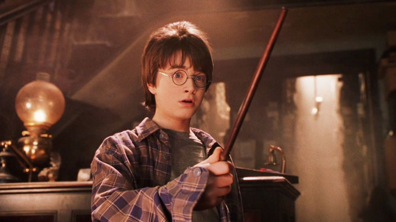 Daniel Radcliffe as Harry Potter holding wand in the wand shop