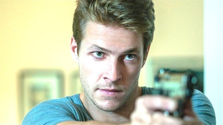Luke Bracey pointing gun