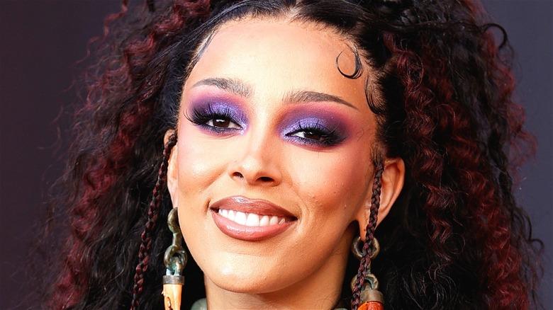Doja Cat with purple eyeshadow smiling