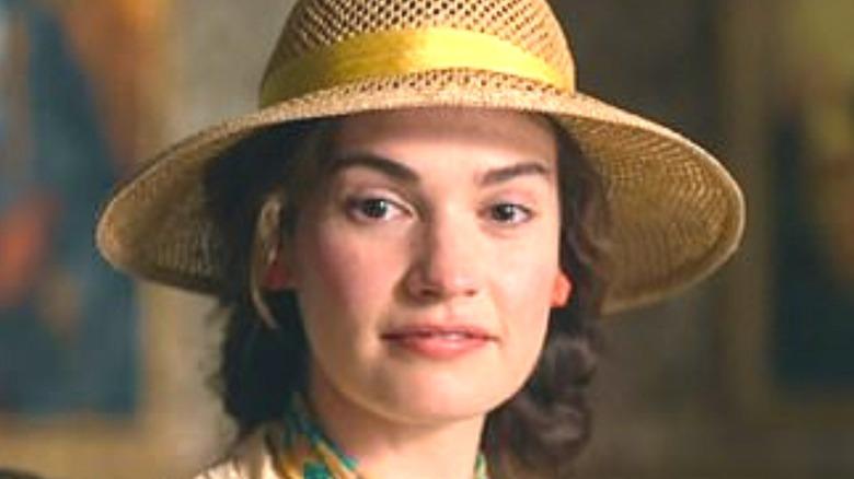 Lily James as Linda Radlett wearing hat
