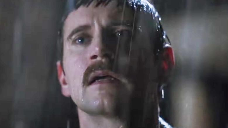 Allen Leech as Paul standing in rain