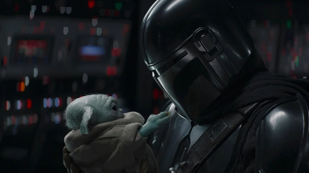 Pedro Pascal Di Djarin holding Baby Yoda Grogu
