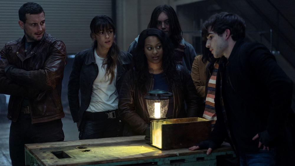 Huck (Annet Mahendru) and Felix (Nico Tortorella) watch Silas perform a trick on The Walking Dead: World Beyond