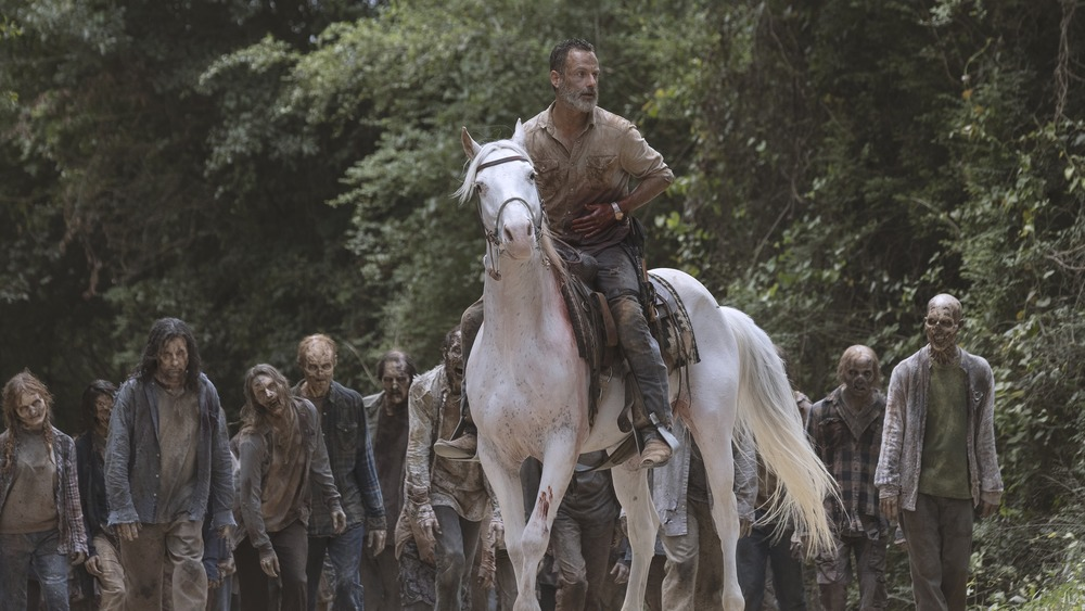 Rick Grimes leading a pack of walkers on horseback on The Walking Dead