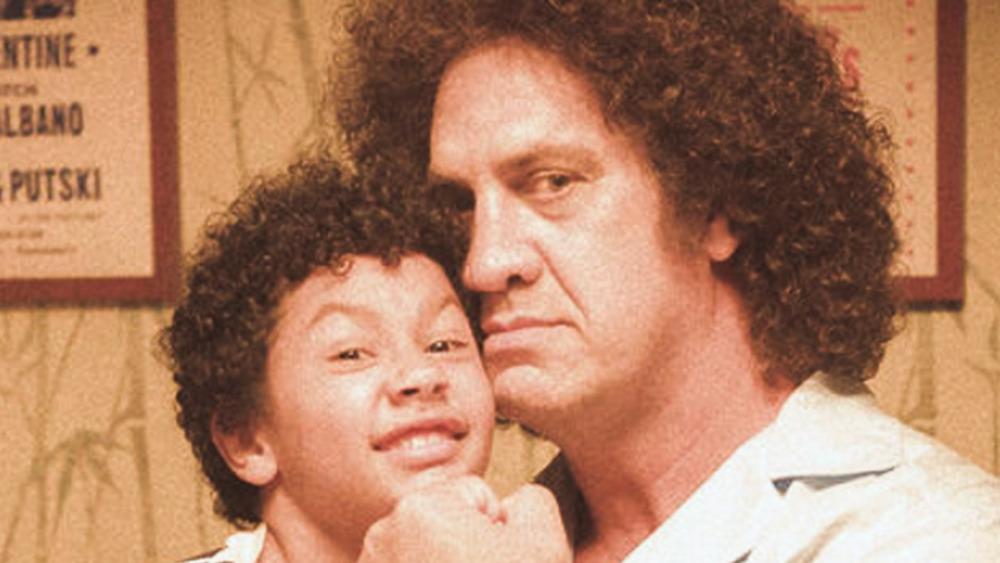 Matthew Willig as Andre the Giant hugging little Dwayne Johnson